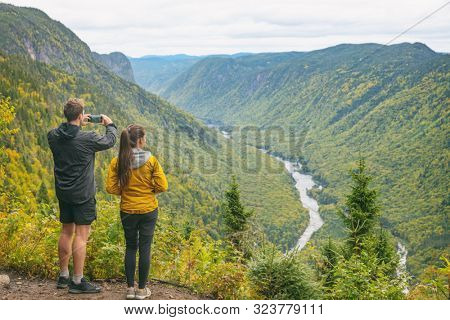 Nature trek hike couple tourists people taking pictures with phone at view of mountain landscape in Autumn forest Canada travel, Jacques Cartier National Park, boreal forest background.