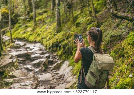 Hiker girl tourist taking picture with mobile phone of trail in nature forest hiking in Quebec outdoors fall autumn season, Canada travel lifestyle. Woman walking with backpack.