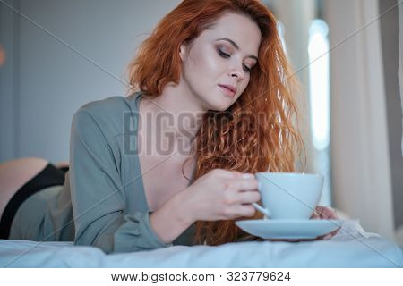morning, leisure, christmas, winter and people concept - happy young woman with cup of coffee or tea in bed at home bedroom