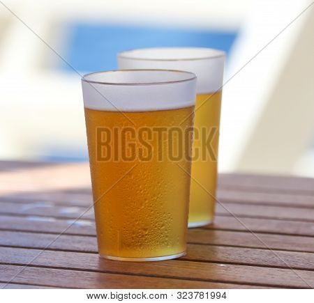 Two Glasses Of Beer On The Table.