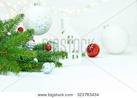 Winter Holidays Decoration Concept. Fir Tree Branch, Decorative Glass Balls And House Toy On White B