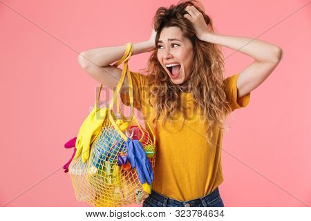 Photo of scared shocked woman in basic t-shirt holding bag with plastic waste and grabbing her head isolated over pink background