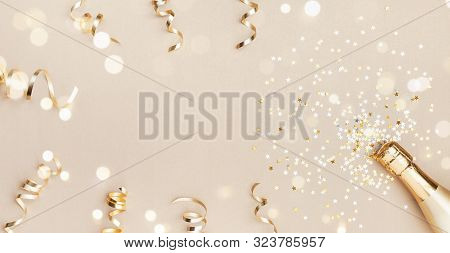 Champagne Bottle With Confetti Stars, Bokeh Decoration And Party Streamers On Golden Background. Chr