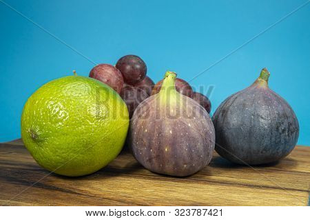 Fresh Tropical Fruit Still Life With Juicy Ripe Purple Figs, Lime And Bunches Of Red Grapes On A Woo