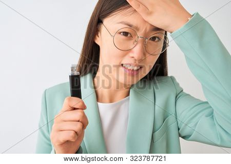 Young chinese businesswoman holding usb memory over isolated white background stressed with hand on head, shocked with shame and surprise face, angry and frustrated. Fear and upset for mistake.