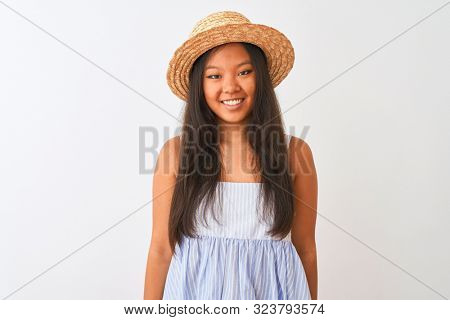 Young chinese woman wearing striped dress and hat standing over isolated white background with a happy and cool smile on face. Lucky person.
