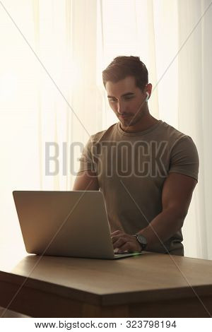 Portrait Of Young Man With Laptop At Table Indoors