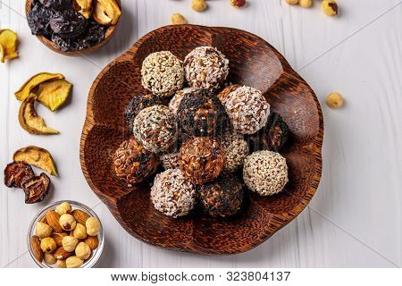 Healthy Energy Balls Of Nuts, Oatmeals And Dried Fruit With Coconut, Flax And Sesame Seeds On Coconu