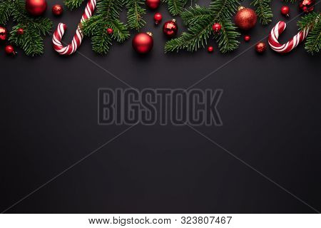 Black Christmas background. Decorative border of fir branches, red Christmas balls and Candy canes. Copy space for text