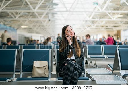 Beautiful Young Woman Talking On Cell Phone At Airport