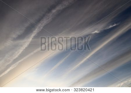 Aircraft Condensation Contrails In The Blue Sky Inbetween Some Clouds