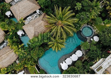 Aerial View Of Luxury Hotel With Straw Roof Villas And Swimming Pools In Tropical Jungle And Palm Tr