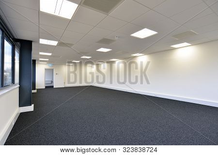 An Empty Office Space With Carpet And Open Door