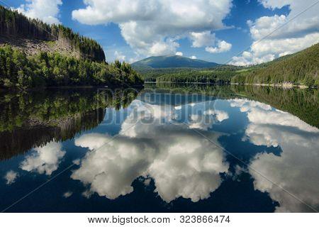 Transalpina Road alpine lake dramatic sky reflection, Romania