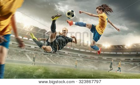 Excitement. Young Female Soccer Or Football Players In Sportwear Kicking Ball For The Goal In Action