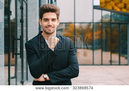 Portrait Of Young Successful Confident Businessman In The City On Office Building Background. Man In