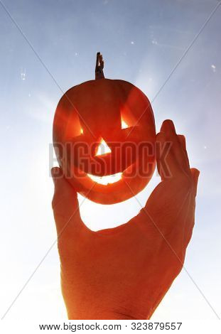 Happy pumpkin like monster in a hand for Halloween