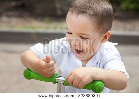 Lovely Small Surprised Smiling Child Boy Riding A Green Trike In The Park. Concept Of Happy Childhoo