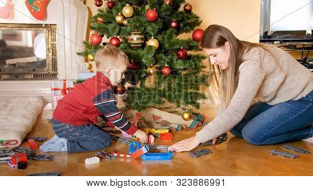 Portrait Of Happy Smiling Little Boy With Mother Building Railroad And Playing With Toy Train On Flo
