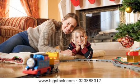 Portrait Of Happy Smiling Family Lying On Floor And Looking At Train Riding On Railroad Under Christ