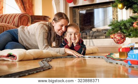 Portrait Of Smiling Mother With Her Little Son Lying On Wooden Floor Under Christmas Tree And Playin