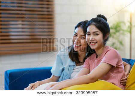 Lgbtq Asian Lasbian Couple Smiling ,looking At Camera And Sitting On Sofa At Living Room At House. A