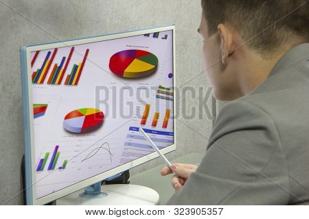 A Young Businessman Sits At A Computer Monitor And Studies A Financial Chart