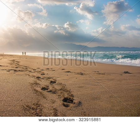 Beautiful Beach With Footprints In The Sand. Couple Of Lovers Walking On The Beach At Sunset And Lea