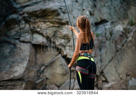 Young Woman Climber Belayer Holding the Rope near the High Rock in the Mountains. Adventure and Extreme Sport Concept