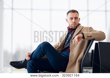 Young Businessman Is Waiting In The Airport Waiting Hall And He Checks The Time On His Watch.