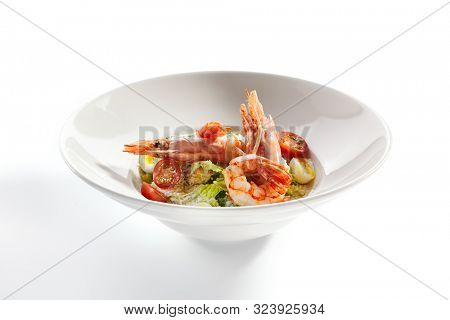 Delicious caesar with argentinian shrimps closeup. North american cuisine restaurant dish, menu item. Tasty salad with natural seafood isolated on white background. Organic lunch, healthy food
