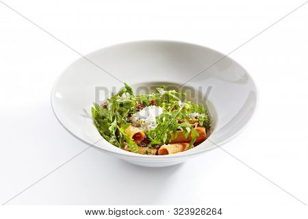 Rigatoni in tomato sauce and stracciatella cheese closeup. Traditional italian cuisine restaurant menu item. Tasty macaroni dish, pasta isolated on white background. Delicious food, gourmet dinner