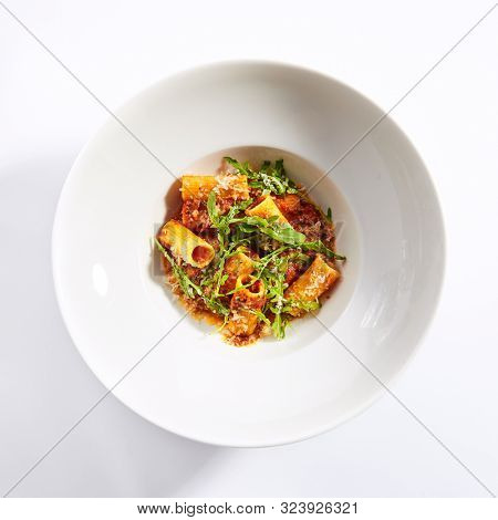 Tasty rigatoni with bolognese sauce top view. Italian cuisine restaurant menu item. Traditional macaroni dish isolated on white background. Delicious food, gourmet dinner, national cooking