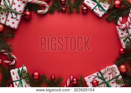 Red Christmas or New Year background. Decorative oval frame of fir branches, gift boxes, Christmas balls and candy cane. Copy space for Christmas creep