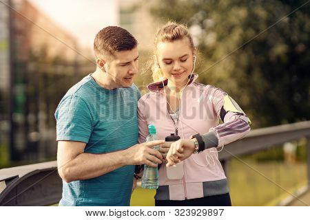 Smiling Couple Checking Time Or Pulse On Heart Rate Monitor Watch - Runners In The Park - Man And Wo