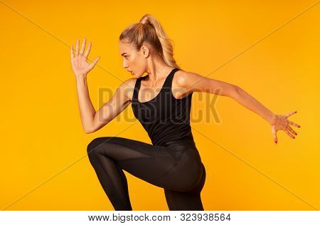 Cardio Workout. Fitness Girl Jumping Working Out Over Yellow Studio Background. Side View