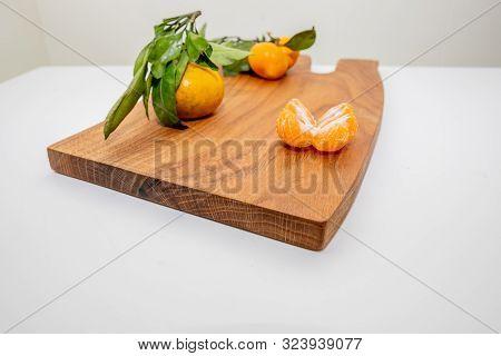 Fresh Juicy Clementine Mandarins, Winter Time Fruits.half-peeled Mandarin And Peel On A Wooden Surfa