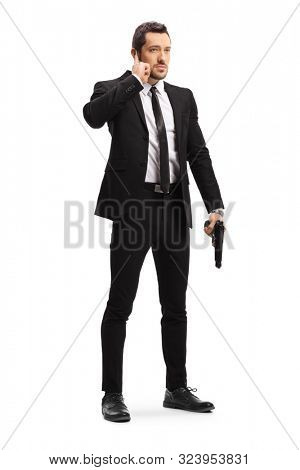 Full length portrait of a bodyguard with a gun isolated on white background