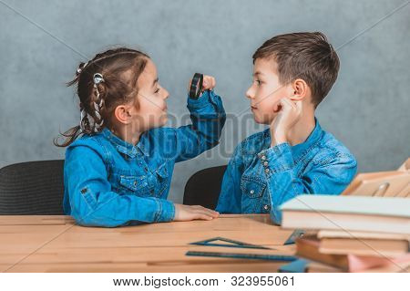 Inquisitive Little Schoolgirl Is Looking Through Magnifying Glass At Something At Her Cute Brother L