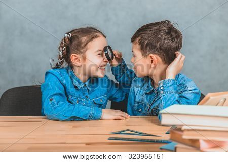 Inquisitive Little Schoolgirl Is Examining Her Brother With A Loupe. Stack Of Books On The Blurred F