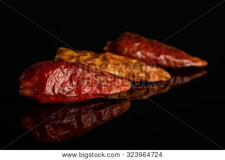 Group Of Three Whole Dry Red Chili Pepper Peperoncino In Row Isolated On Black Glass