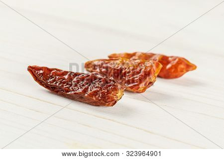 Group Of Three Whole Dry Red Chili Pepper Peperoncino In Row On White Wood