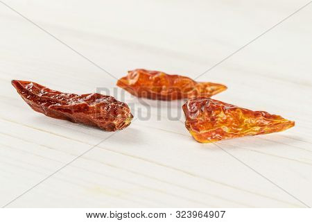 Group Of Three Whole Dry Red Chili Pepper Peperoncino On White Wood