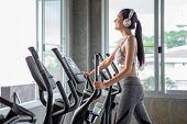 Beautiful young asian woman exercise on elliptical machine and listening music with headphones relaxtion time in fitness gym . sport girl workout , training, healthy lifestyle poster