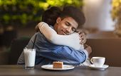 Peaceful beloved mixed race couple hugging with affection at cafe, copy space poster