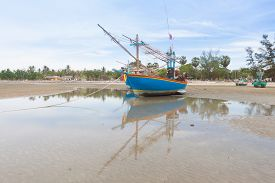 Wooden Fishing Boat On The  Low Tide Beach