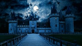 Haunted Gothic Castle At Night. Old Spooky House In Full Moon. Creepy View Of Dark Mystery Castle Wi