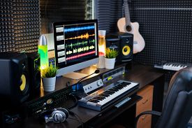 Electrical equipment for music recording and computer monitor with sound mixing tracks on workplace of deejay or modern musician in studio
