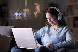 Happy Girl Wearing Headphones Watching And Listening Videos On Laptop Sitting On A Couch In The Nigh