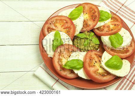 Mozzarella Cheese And Tomatoes Are Also Laid Out On Plates. Caprese Salad - Tomato, Mozzarella, Basi